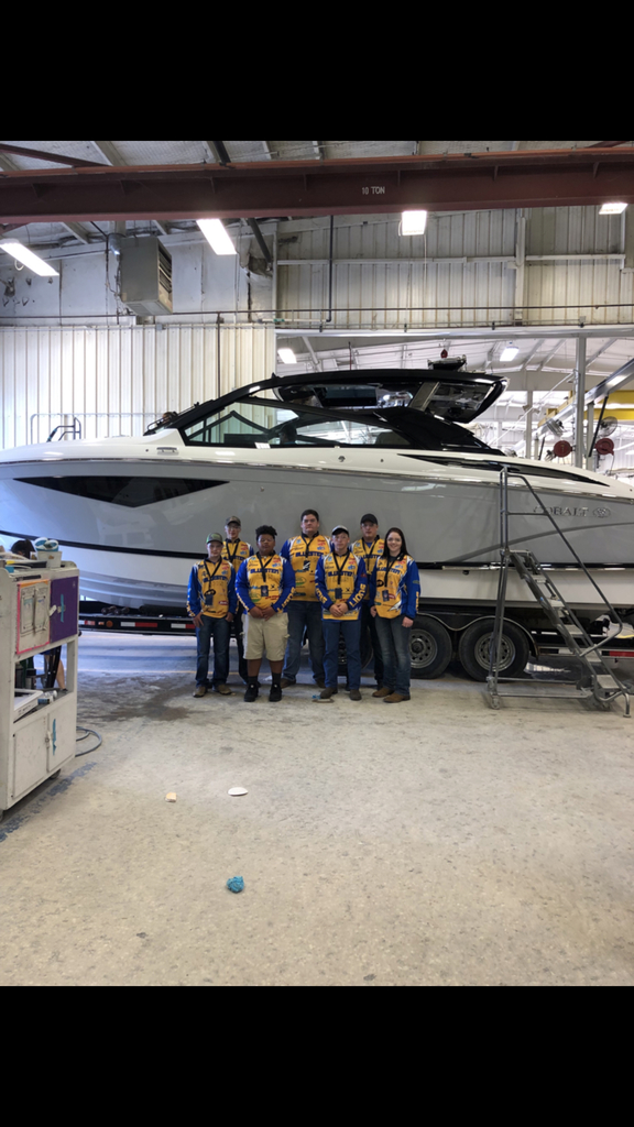 The Bluestem fishing team standing in front of a finish boat at Cobalt Boats.